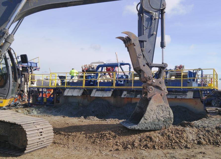 A backhoe and the mud handling unit. Dirt is separated from the drilling mud so drilling mud can be reused.