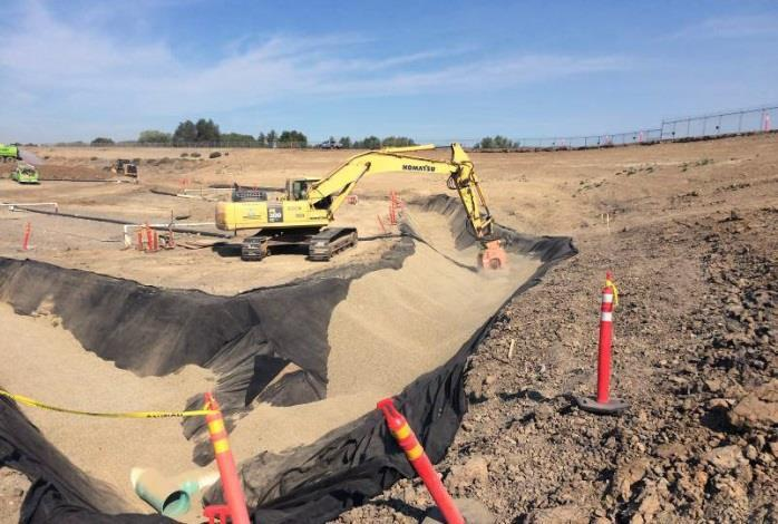 Excavator compacting drain rock at toe of northern jurisdictional levee (September 2015)