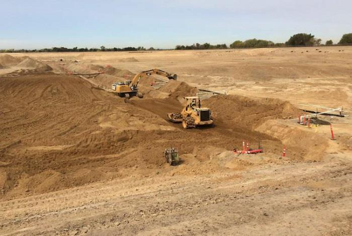 Excavator and sheepsfoot backfilling and compacting underdrain collector trench (September 2015)