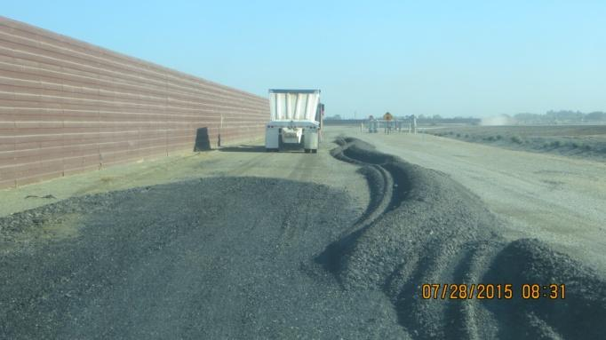Asphalt grindings from a previously demolished area are reused along new fenceline (July 2015)